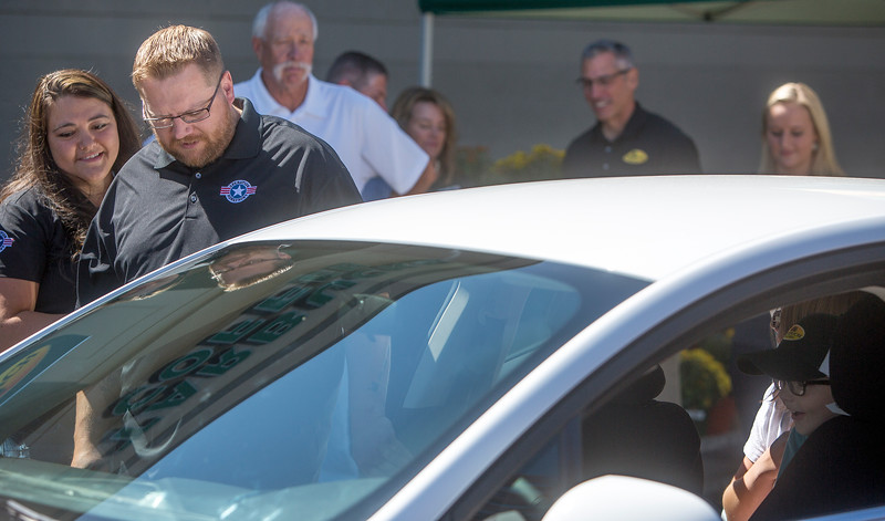 Angela Walter and Daniel Walter look at their new car while Hunter Walter, 8, checks out the inside at Safeway in Fountain, Colo. on Monday, Sept. 18, 2017. Safeway partnered with Eckrich and Operation Homefront to give the Walters the new Ford Fusion.<br /> (The Gazette, Nadav Soroker)