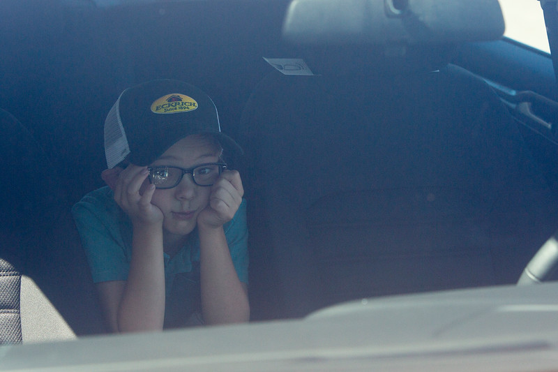 Hunter Walter, 8, rests inside the family's new Ford Fusion while his parents talk to the media outside of Safeway in Fountain, Colo. on Monday, Sept. 18, 2017. The Walters were given the new car by Safeway and Eckrich.<br /> (The Gazette, Nadav Soroker)