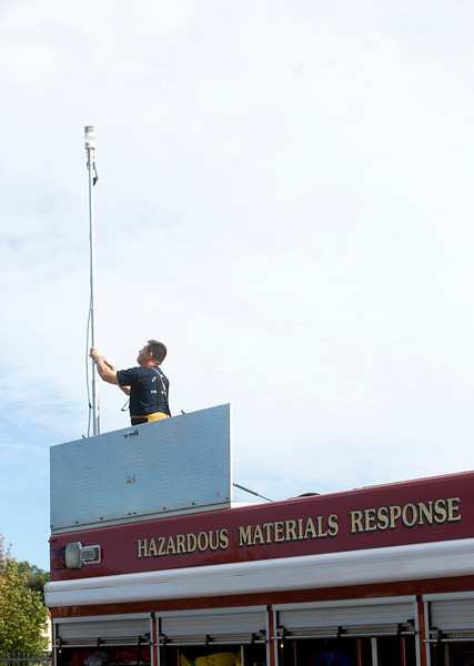 A firefighter brings down an antenna on the back of the Hazardous Materials engine during practice at CSFD headquarters in Colorado Springs, Colo. on Friday, Sept. 22, 2017. The engine can connect to local information networks to allow firefighters to track hazardous materials and monitor incidents.<br /> <br /> (The Gazette, Nadav Soroker)