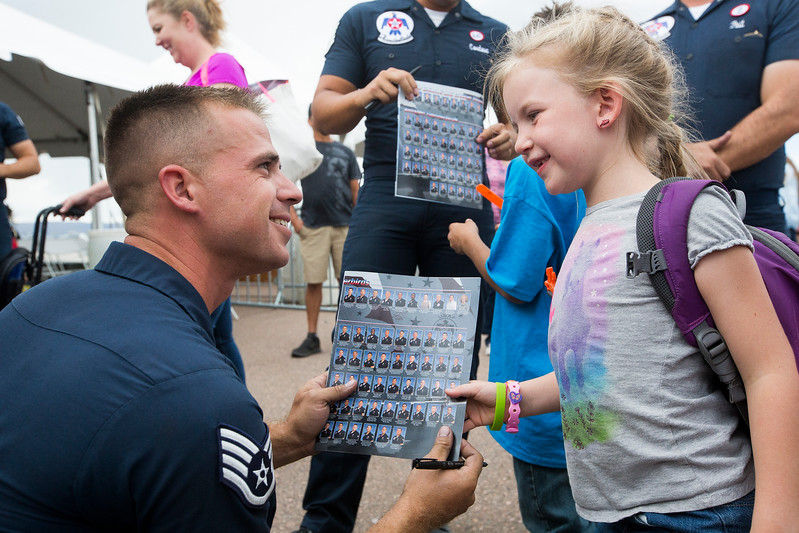 Penny Herndon, 7, receives a signed roster from SSgt. Kyle Smith during a meet and greet at the High Flight day at Pikes Peak Regional Airshow on Friday, Sept. 22, 2017. After the airshow the pilots came out to meet the kids that watched their practice runs.<br /> <br /> (The Gazette, Nadav Soroker)