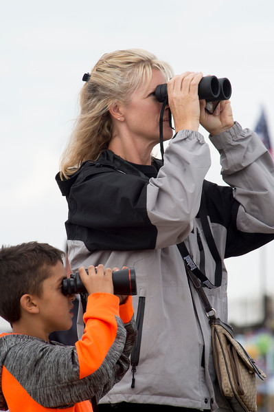 Kim Goranson and Joseph Sidhu, 7, watch planes fly by at the Pikes Peak Regional Airshow on Saturday, Sept. 23, 2017. Planes would buzz the crowd as close as possible but binoculars or large camera lenses still helped.<br /> <br /> (The Gazette, Nadav Soroker)