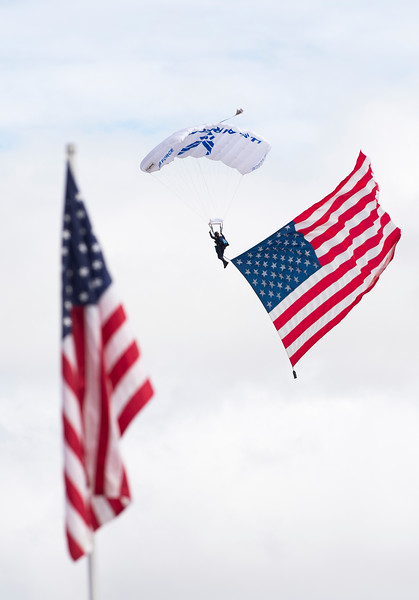 A member of the Air Force's Wings of Blue parachutes down to the airshow with a large American flag at the Pikes Peak Regional Airshow on Saturday, Sept. 23, 2017. The Wings of Blue opened up the flights for the day.<br /> (The Gazette, Nadav Soroker)