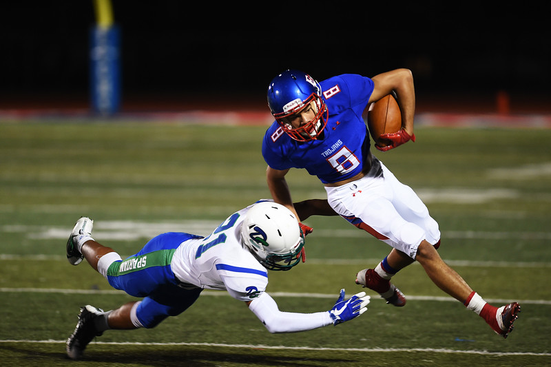 Trojan Jalen Lyon tries to pass Spartan Jose Handford at Fountain-Fort Carson on Friday, Sept. 29, 2017.<br /> <br /> (The Gazette, Nadav Soroker)
