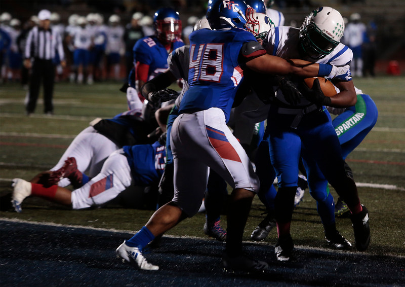 Doherty Spartan Julian Cooks enters the end-zone while Fountain-Fort Carson Senior Iosua Maika tries to hold him back at Fountain-Fort Carson on Friday, Sept. 29, 2017.<br /> <br /> (The Gazette, Nadav Soroker)