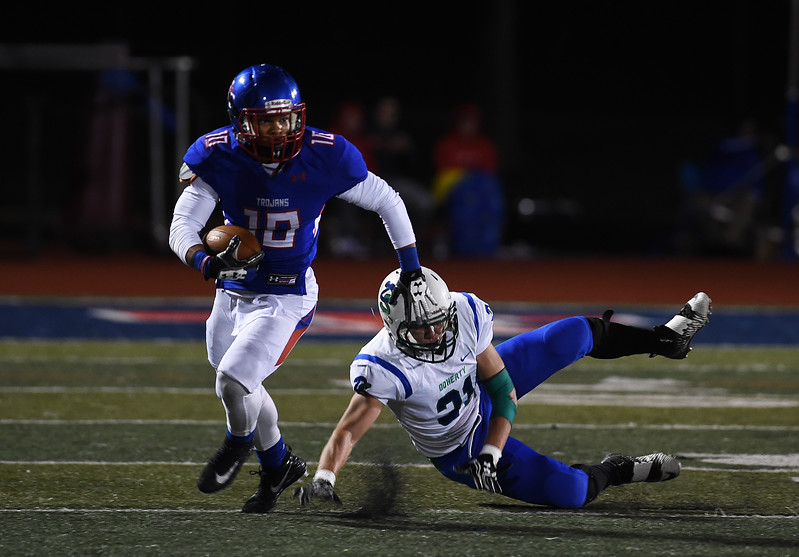 Trojan senior Gavin Green stiff-arms past a Spartan before getting tackled up field at Fountain-Fort Carson on Friday, Sept. 29, 2017.<br /> <br /> (The Gazette, Nadav Soroker)