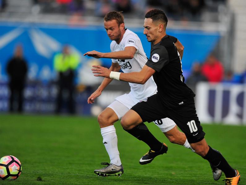 Switchbacks midfielder Masta Kacher races past Orange County FC midfielder Frank Olijve with the ball at Wiedner Field on Saturday, Sept. 30, 2017.<br /> <br /> (The Gazette, Nadav Soroker)
