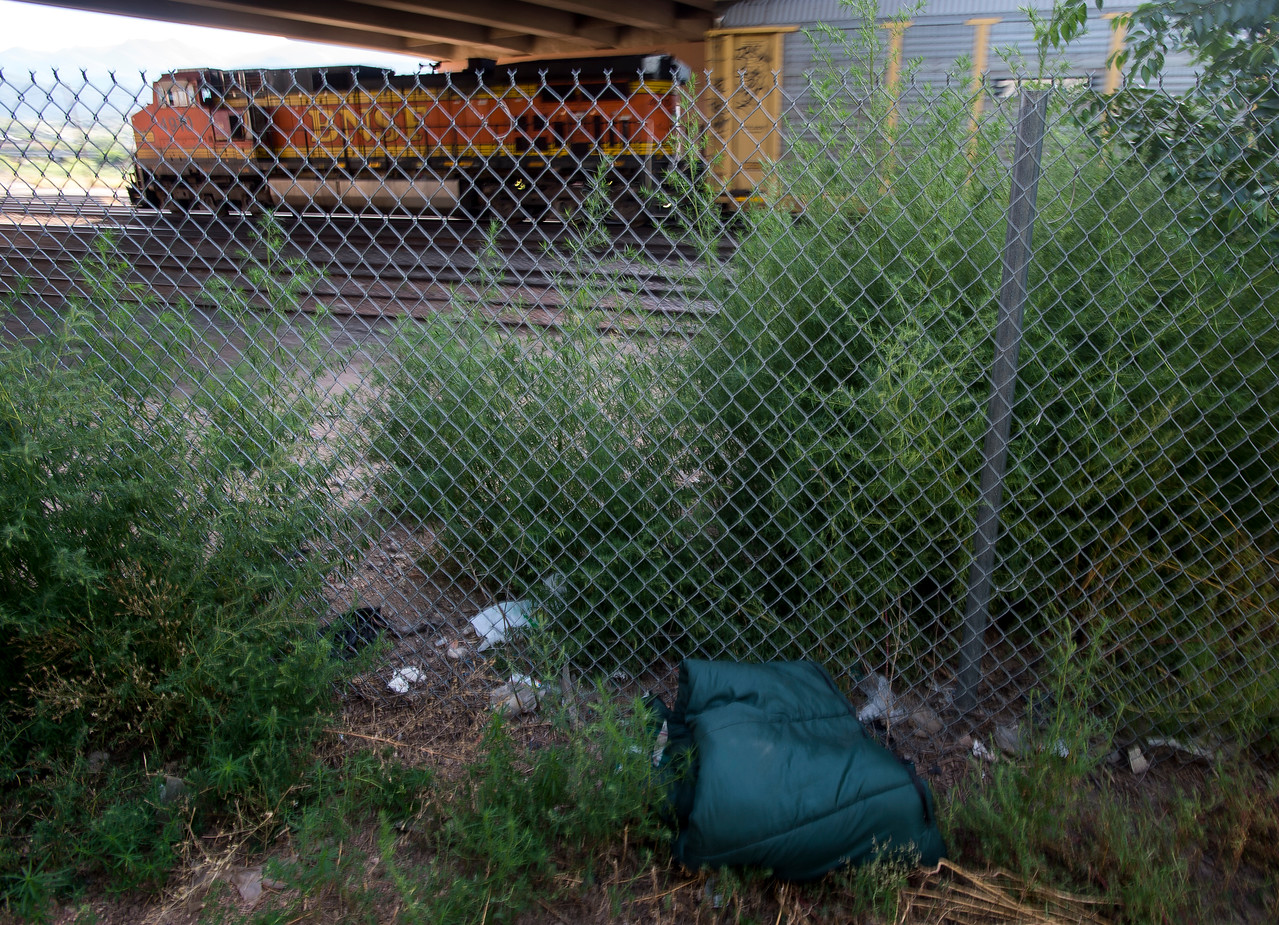 A sleeping bag lays against a fence at the bottom of Monument Valley Park as a train passes nearby. Four people have been killed by trains in El Paso County in the past three months, three of the four were experiencing homelessness.<br /> (The Gazette, Nadav Soroker)