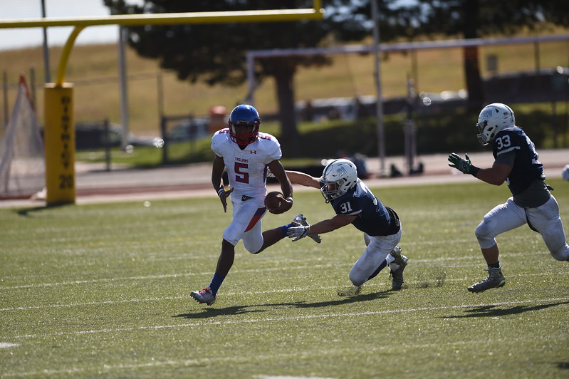 Eric Donnell runs out of the grasp of Rece Rowan and Sam Miller at Liberty High School in Colorado Springs, Colo. on Saturday, Sept. 16, 2017. <br /> <br /> (The Gazette, Nadav Soroker)