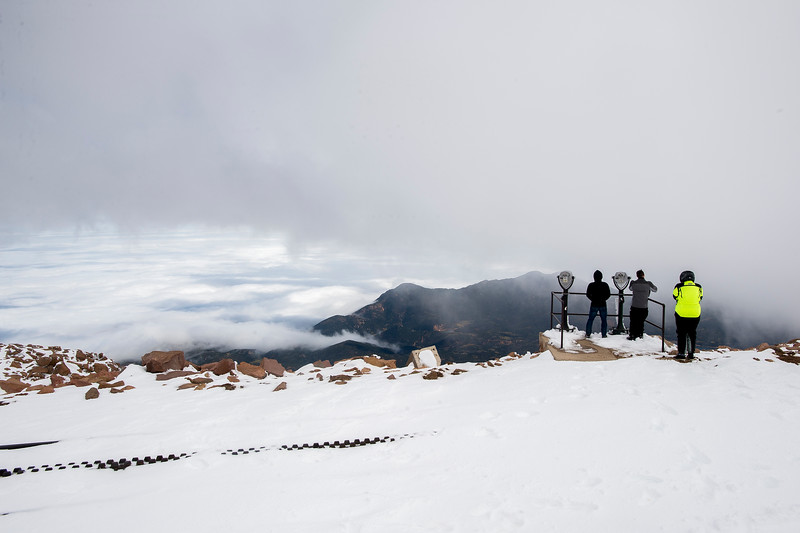 Tim Le, Ben Waters and Crystal Hansen look out over the clouds covering Colorado Springs, Colo., from the summit of 14,115 ft. Pikes Peak on Friday, Sept. 29, 2017. The sun occasionally broke through the clouds on top of the mountain.<br /> <br /> (AP Photo/The Gazette, Nadav Soroker)