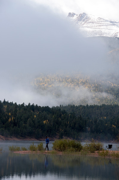 Bryan Hale walks along the shore of Crystal Creek Reservoir while waiting for fish to bite on Friday, Sept. 29, 2017. The road up to Pikes Peak emerges from the clouds beyond the reservoir.<br /> <br /> (The Gazette, Nadav Soroker)