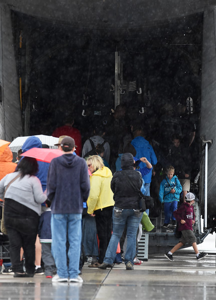 Visitors wait for a tour under the tail of a C-130 on display at the Pikes Peak Regional Airshow while rain pours down on Saturday, Sept. 23, 2017. Rain canceled the afternoon flights and closed the tarmac.<br /> <br /> (The Gazette, Nadav Soroker)