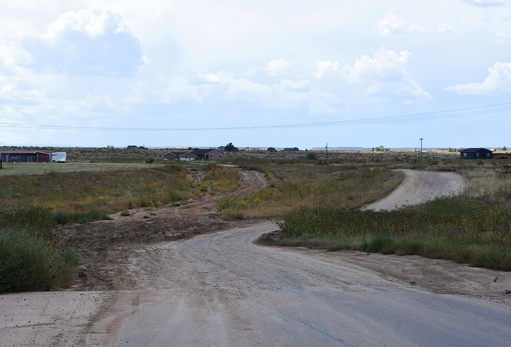 The paved section of Boca Raton Heights ends and continues as a dirt road to the left on Thursday, Sept. 14, 2017. Community members have cut a new road through private land to the right after the original road became nearly impassable.<br /> <br /> (The Gazette, Nadav Soroker)