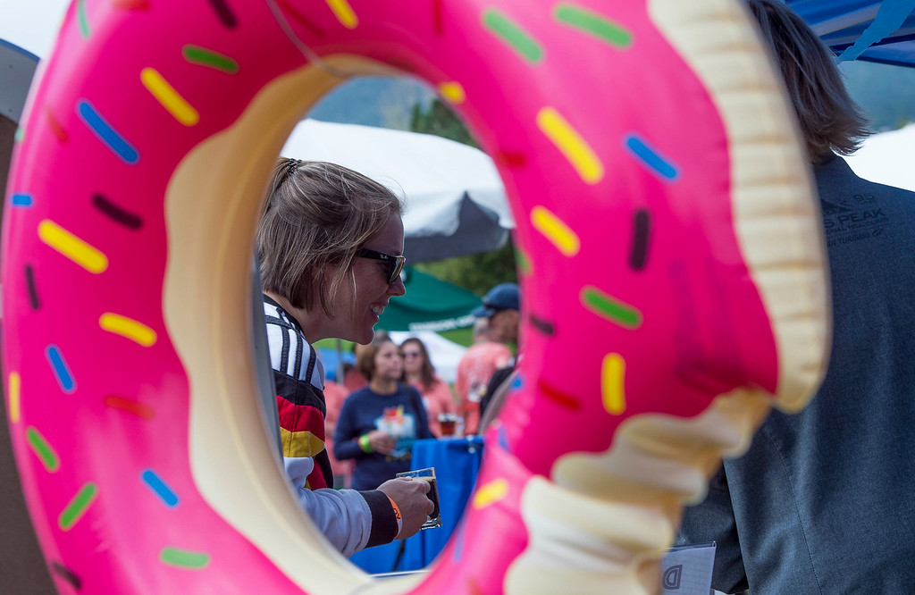 Sara Nicholson picks out a donut to pair with her root beer at Pawtoberfest 2017 in Bear Creek Regional Park in Colorado Springs, Colo. on Saturday, Sept. 16, 2017. Vendors provided non-alcoholic options for those who didn't want to drink.<br /> <br /> (The Gazette, Nadav Soroker)