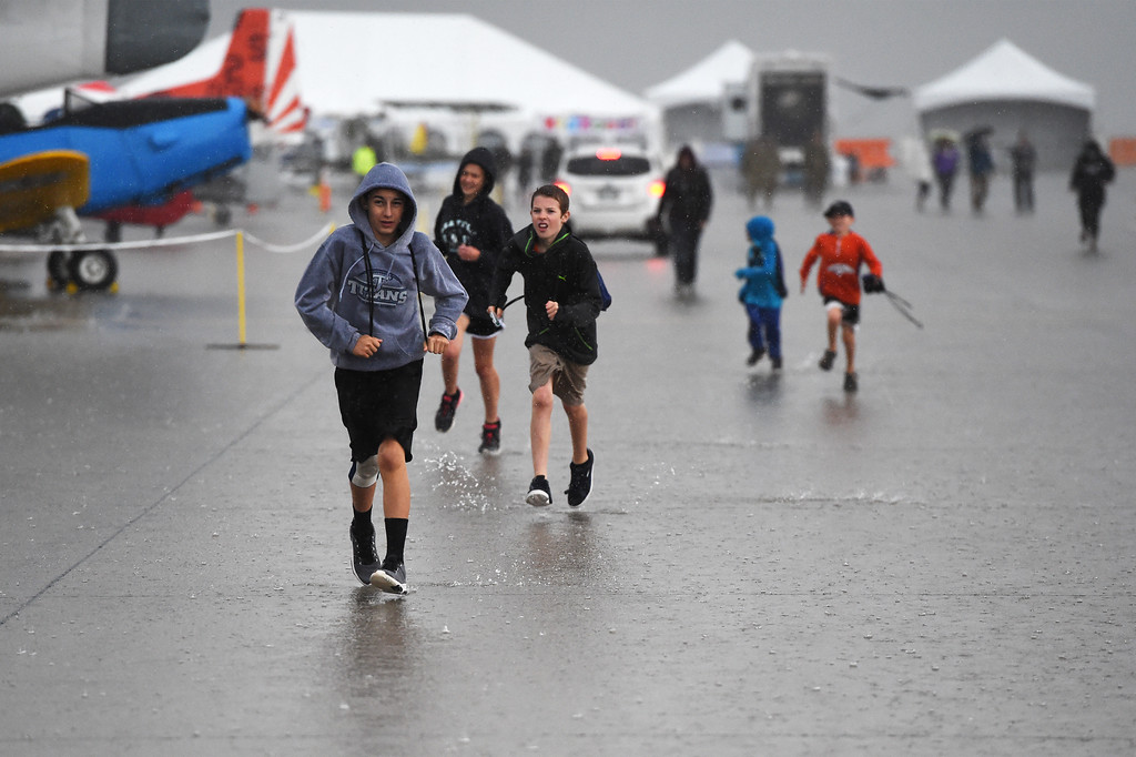 People run through the rain at the Pikes Peak Regional Airshow as security started closing the display aircraft on Saturday, Sept. 23, 2017. Crews kept the aircraft open as long as possible to let people explore and stay dry.<br /> <br /> (The Gazette, Nadav Soroker)