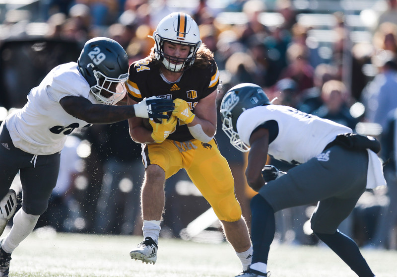 Cowboys running back Brett Benton tries to squeeze through Wolf Pack defenders as the Wyoming Cowboys take on the Nevada Wolf Pack Saturday, Oct. 26, 2019 at War Memorial Stadium. Wyoming defeated Nevada 31-3. Nadav Soroker/Wyoming Tribune Eagle