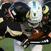 South defenders Macarius Wright (4) and Zayne Vankirk (21) sandwich a Kelly Walsh player Friday, September 13, 2019 at South High School. The Bison lost to the Trojans 8-47. Nadav Soroker/Wyoming Tribune Eagle