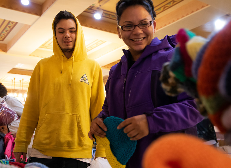 Nita Barragan and her husband Tristan Barragan pick out hand knit caps for their kids, nieces and nephews at the Coats for Kids event Friday, October 4, 2019 at the Cheyenne Depot. Volunteers with Ewe Count donated more than 700 knit caps for the event. Nadav Soroker/Wyoming Tribune Eagle