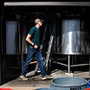 Assistant brewer Jake Bauer walks past the mash tun and the boil kettle after cleanup from brewing a Vienna Oatmeal Blonde Ale with head brewer Mitch Kunce Tuesday, October 8, 2019 at The Library Sports Grille and Brewery. Nadav Soroker/Laramie Boomerang