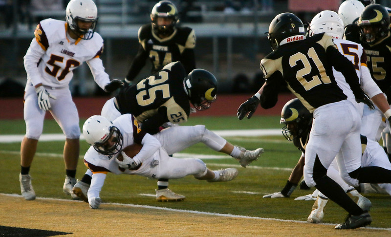Laramie running back Isaac Sell (21) dives under Cheyenne South defensive back Jadyn Cummings (25) for a touchdown Friday, October 11, 2019 at South High School. The Bison defeated the Laramie High School Plainsmen 36-35. Nadav Soroker/Wyoming Tribune Eagle