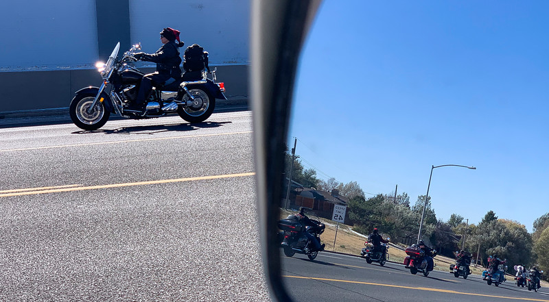 A motorcycle rider cruises by in line with the rest of the 42nd annual Toy Run seen in a rear view mirror Saturday, October 12, 2019 near High Country Harley-Davidson. The annual ride gathers toys for the Salvation Army Cheyenne Corps. Nadav Soroker/Wyoming Tribune Eagle