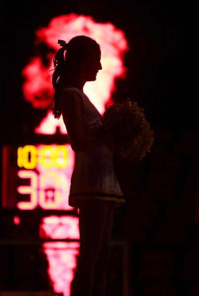 A Wyoming cheerleader is silhouetted by a burst of fire as the Cowgirls take to the court Friday, Nov. 1, 2019 at Arena-Auditorium. The Wyoming Cowgirls host the Adams State Grizzlies for the season's opening exhibition match. Nadav Soroker/Laramie Boomerang