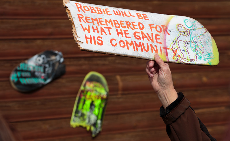 An attendee of the anniversary memorial for Robbie Ramirez holds up a broken skateboard painted with a message of remembrance Monday, Nov. 4, 2019 at Ramirez's former apartment. Other broken and decorated skateboards were hung on the wall, all of them donated by Ramirez's friends and painted by Amanda Pittman. Nadav Soroker/Laramie Boomerang