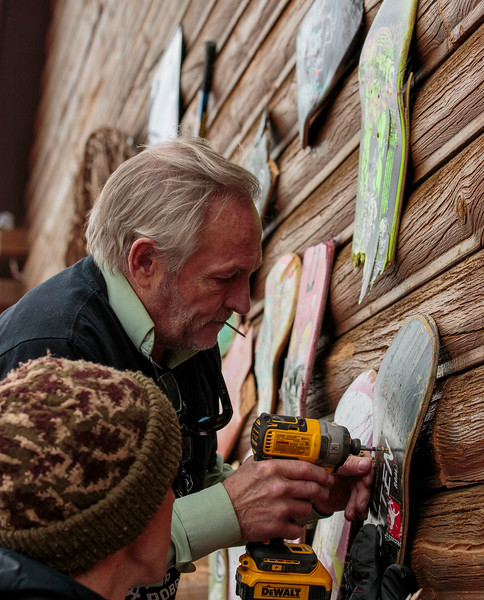 David Bunn, Robbie Ramirez's uncle, screws broken and decorated skateboards painted with messages of remembrance onto the wall Monday, Nov. 4, 2019 at Ramirez's former apartment. Broken and decorated skateboards were hung on the wall, all of them donated by Ramirez's friends and painted by Amanda Pittman. Nadav Soroker/Laramie Boomerang