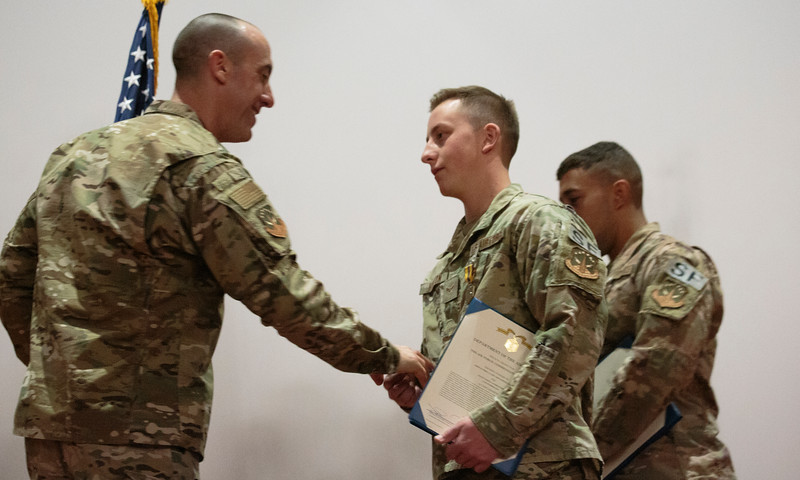 Col. Damian Schlussel, left, shakes hands and gives a challenge coin to Airman First Class Cristopher Horton, a security forces member at F.E. Warren, for saving a Nebraska family from a house fire during a patrol Friday, Nov. 15, 2019 at F.E. Warren. Nadav Soroker/Wyoming Tribune Eagle