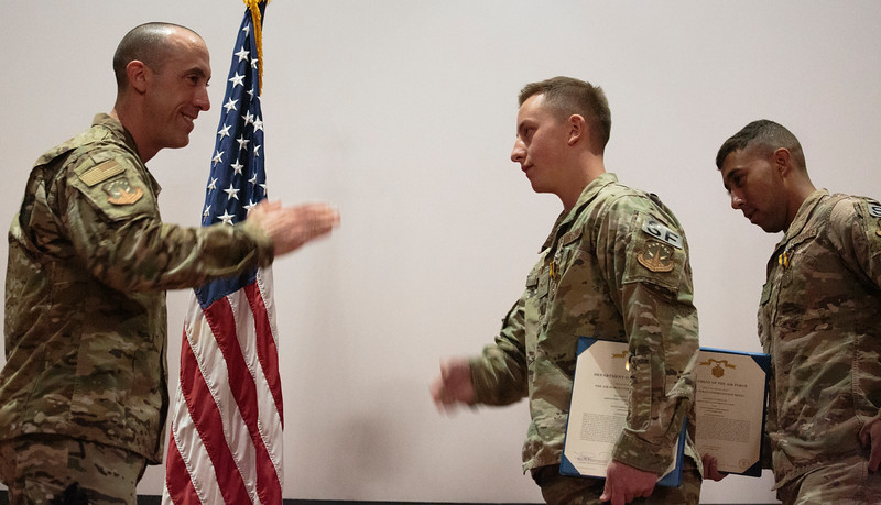 Col. Damian Schlussel, left, salutes Airman First Class Cristopher Horton, a security forces member at F.E. Warren, after giving him an Air Force Commendation Medal and a challenge coin for saving a Nebraska family from a house fire during a patrol Friday, Nov. 15, 2019 at F.E. Warren. Airman First Class Christian Reed, right, was on patrol with Horton and also received an Air Force Commendation Medal and challenge coin. Nadav Soroker/Wyoming Tribune Eagle