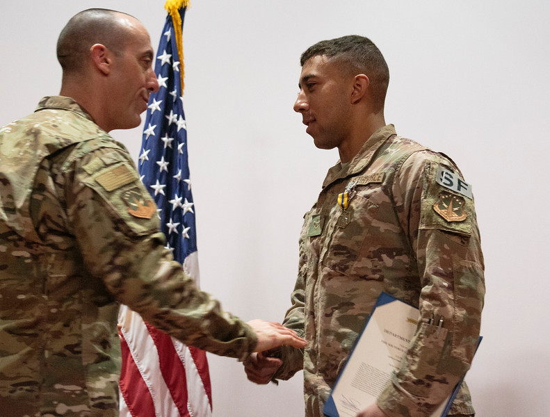 Col. Damian Schlussel, left, shakes hands and gives a challenge coin to Airman First Class Christian Reid, a security forces member at F.E. Warren, for saving a Nebraska family from a house fire during a patrol Friday, Nov. 15, 2019 at F.E. Warren. Nadav Soroker/Wyoming Tribune Eagle