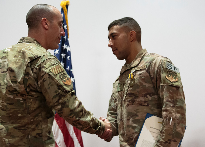 Col. Damian Schlussel, left, shakes hands and gives a challenge coin to Airmen First Class Christian Reid, a security forces member at F.E. Warren, for saving a Nebraska family from a house fire during a patrol Friday, Nov. 15, 2019 at F.E. Warren. Nadav Soroker/Wyoming Tribune Eagle
