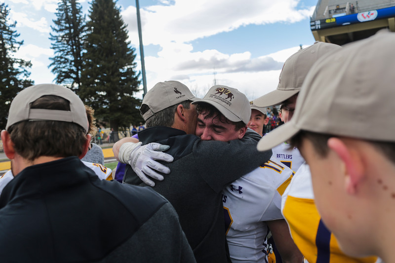 Little Snake River's Riggen Myers hugs a coach after taking the trophy in the WHSAA Six Man championship match between Little Snake River and HEM Saturday, Nov. 16, 2019 at War Memorial Stadium. The Rattlers defeated the Miners 71-38 to clinch the state championship. Nadav Soroker/Wyoming Tribune Eagle