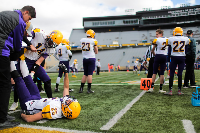 Little Snake River's Wyatt Duncan, left, stretches out with help from his team as he catches a break on the sidelines in the WHSAA Six Man championship match between Little Snake River and HEM Saturday, Nov. 16, 2019 at War Memorial Stadium. The Rattlers defeated the Miners 71-38 to clinch the state championship. Nadav Soroker/Wyoming Tribune Eagle