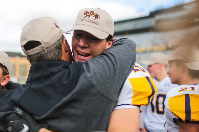 Little Snake River's Wyatt Duncan hugs a coach after winning in the WHSAA Six Man championship match between Little Snake River and HEM Saturday, Nov. 16, 2019 at War Memorial Stadium. The Rattlers defeated the Miners 71-38 to clinch the state championship. Nadav Soroker/Wyoming Tribune Eagle