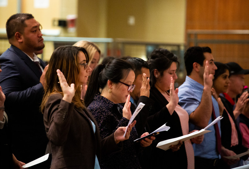 Irene Checa, front left, and sixteen other new citizens take the Oath of Citizenship at the naturalization ceremony  Monday, Nov. 18, 2019 at Cheyenne South High School. Nadav Soroker/Wyoming Tribune Eagle