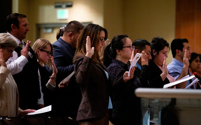 Irene Checa, center, and sixteen other new citizens take the Oath of Citizenship at the naturalization ceremony  Monday, Nov. 18, 2019 at Cheyenne South High School. Nadav Soroker/Wyoming Tribune Eagle