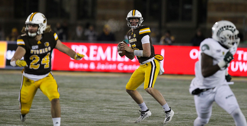 Wyoming quarterback Levi Williams looks for an open teammate before scrambling with the ball Friday, Nov. 22, 2019 at War Memorial Stadium. The Wyoming Cowboys are tied with the Colorado State Rams 7-7 in the Border War. Nadav Soroker/Laramie Boomerang