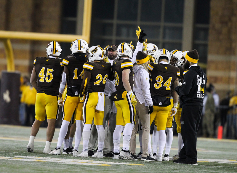 Wyoming players raise hands during a huddle Friday, Nov. 22, 2019 at War Memorial Stadium. The Wyoming Cowboys are tied with the Colorado State Rams 7-7 in the Border War. Nadav Soroker/Laramie Boomerang