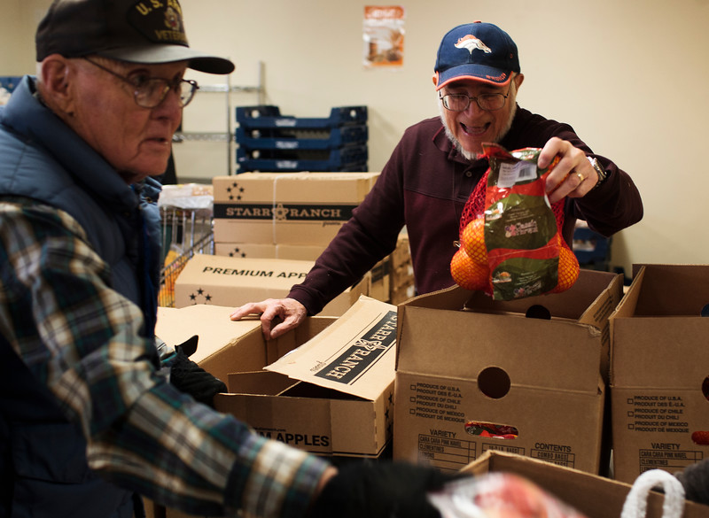 Lloyd Osborn, left, and Louie Rodriguez, volunteers at the St. Joseph's Food Pantry, add fresh apples and oranges to the boxes given to about 450 families in need to help them get through Thanksgiving  Monday, Nov. 25, 2019 at the St. Joseph's Food Pantry. The Turkey Boxes come with the bird, as well as all the fixings to get through Thanksgiving, and are made with donations from big groups like Albertsons, Spradley Barr and the St. Mary's Youth Group, as well as from smaller groups and individuals, according to Pantry Coordinator Renee Gamino. Nadav Soroker/Wyoming Tribune Eagle