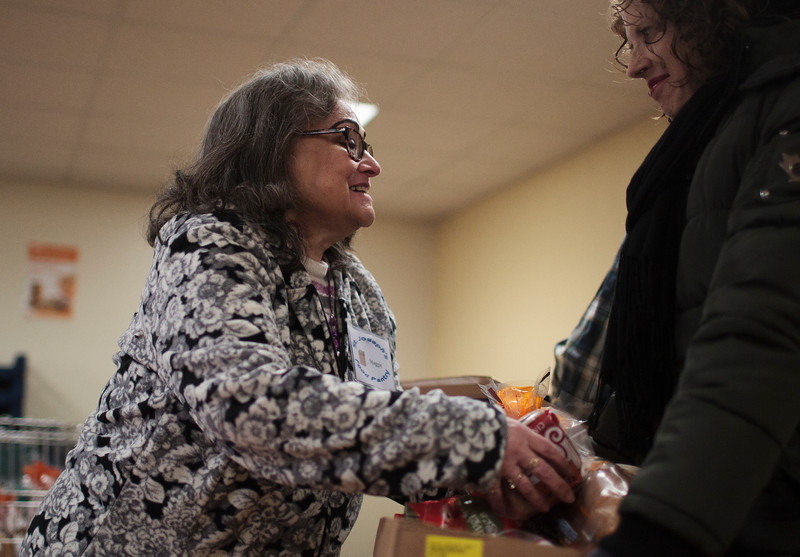 Volunteer Maggie Rodriguez adds loaves of bread to a Turkey Box carried by fellow volunteer Cathy Wright for a family in need Monday, Nov. 25, 2019 at the St. Joseph's Food Pantry. The Turkey Boxes come with the bird, as well as all the fixings to get through Thanksgiving, and are made with donations from big groups like Albertsons, Spradley Barr and the St. Mary's Youth Group, as well as from smaller groups and individuals, according to Pantry Coordinator Renee Gamino. Nadav Soroker/Wyoming Tribune Eagle