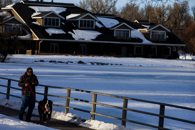 Jeffrey Brincks walks his Bernese Mountain Dog Abram along the trail around Sloan Lake Monday, Dec. 2, 2019 at Lions Park. After a week of snowstorms Cheyenne should experience a mild, snow-free week according to the National Weather Service. Nadav Soroker/Wyoming Tribune Eagle