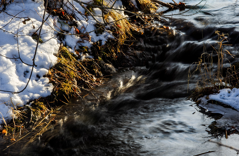 Meltwater flows down a creek past snow-covered banks and into Sloan Lake Monday, Dec. 2, 2019 at Lions Park. After a week of snowstorms Cheyenne should experience a mild, snow-free week according to the National Weather Service. Nadav Soroker/Wyoming Tribune Eagle