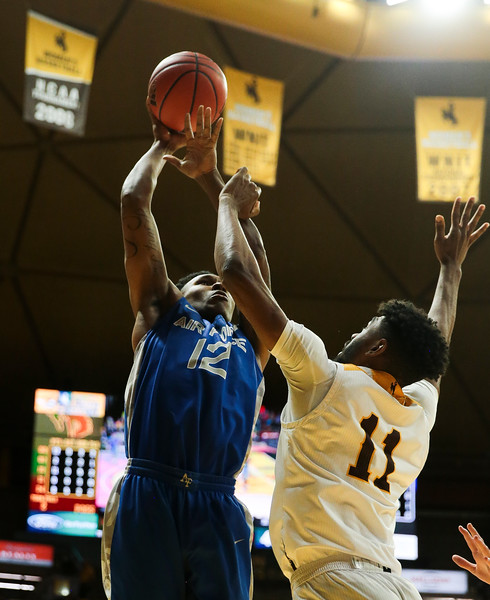 "Air Force forward Lavelle Scottie (12) attempts a shot over Wyoming's Trevon ""TJ"" Taylor (11), Wednesday, Dec. 4, 2019 in Arena-Auditorium. University of Wyoming Mens Basketball lose to Air Force Academy 86-77. Nadav Soroker/Laramie Boomerang"