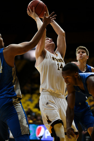 Wyoming forward Austin Mueller (14) grabs a rebound amidst Air Force players, Wednesday, Dec. 4, 2019 in Arena-Auditorium. University of Wyoming Mens Basketball lose to Air Force Academy 86-77. Nadav Soroker/Laramie Boomerang