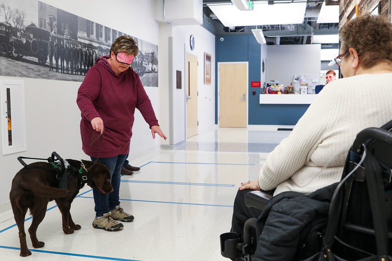 Michelle Woerner, the CEO of K9s 4 Mobility and member of the Mayor's Council for People with Disabilities, works with Bulldogger to try navigating the mockup of a bathroom in the new Municipal Court Building, Friday, Dec. 6, 2019 at the Cheyenne Public Safety Center. After taping out the plan, council members voiced concerns on spacing and tried navigating the space so the architect and Hornak could see potential challenges. Nadav Soroker/Wyoming Tribune Eagle