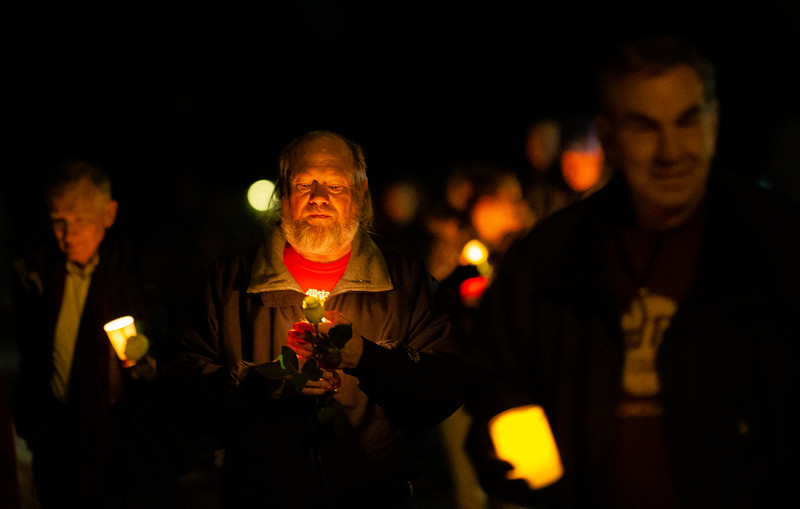 "William Shaver, center, carries a white flower and lit candle for his son Michael as people walk to the Christmas Box Angel to remember lost loved ones, Friday, Dec. 6, 2019 in Lakeview Cemetery. The event, inspired by the Richard Paul Evans novel ""The Christmas Box"" is a chance for people to remember children and other family members who have passed. Nadav Soroker/Wyoming Tribune Eagle"