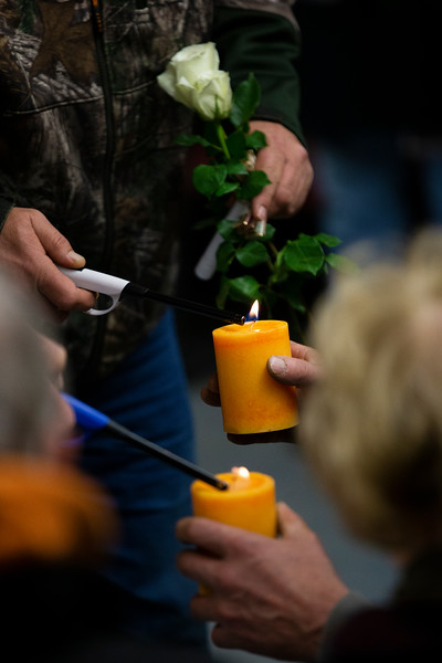 "An attendee helps another light their candle as people gather to remember lost loved ones during a candlelight vigil at the Christmas Box Angel, Friday, Dec. 6, 2019 in Lakeview Cemetery. The event, inspired by the Richard Paul Evans novel ""The Christmas Box"" is a chance for people to remember children and other family members who have passed. Nadav Soroker/Wyoming Tribune Eagle"