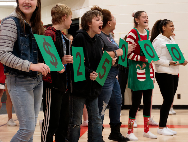 Students Rachel Price, John Quigley, Skylar Rohaley, Jorieauna Lipscomb, Avery Brinkman and Khiana Fields hold up signs for the unrestricted $25,000 award given to Principal Brian Cox as the only 2019 Milken Educators Award recipient in Wyoming Monday, Dec. 9, 2019 at Johnson Junior High School. The Milken Award recognizes achievements by early- and mid-career educators while encouraging their future accomplishments with the financial award. Nadav Soroker/Wyoming Tribune Eagle