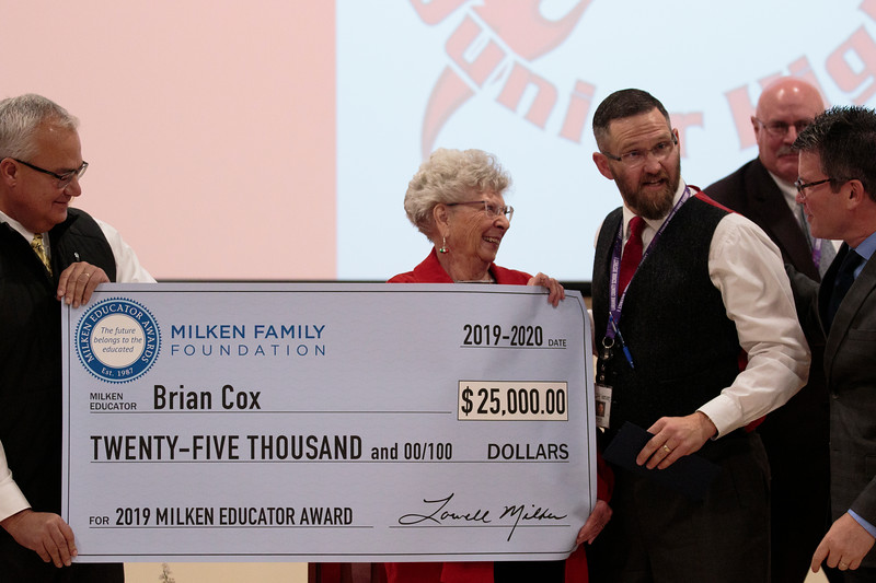Principal Brian Cox, right, is given a large check for an unrestricted $25,000 award as the only 2019 Milken Educators Award recipient in Wyoming Monday, Dec. 9, 2019 at Johnson Junior High School. The Milken Award recognizes achievements by early- and mid-career educators while encouraging their future accomplishments with the financial award. Nadav Soroker/Wyoming Tribune Eagle