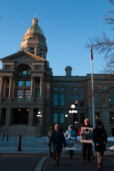 Marchers carry signs during a circuit around the capitol in support of repealing the death penalty in Wyoming Monday, Dec. 9, 2019 in Cheyenne. About twenty other marchers in a circuit of the capitol before marching down Capitol Street. Nadav Soroker/Wyoming Tribune Eagle